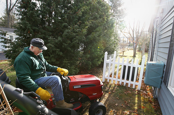"""Record-Eagle/Keith King<br /> Andy Lundberg, of Traverse City, and a World War II veteran who retired after 28 years with the United States Navy, rakes leaves in his yard Tuesday, November 29, 2011 prior to using his riding lawnmower to pick them up in his yard. """"It was cold out so I went in to get my mittens,"""" Lundberg said. """"The wind doesn't help,"""" Lundberg said, after seeing leaves he'd raked blowing toward his neighbor's house. """"I thought that was the last time,"""" Lundberg said after he recalls raking leaves, for what he thought was the last time, before a recent snowfall."""