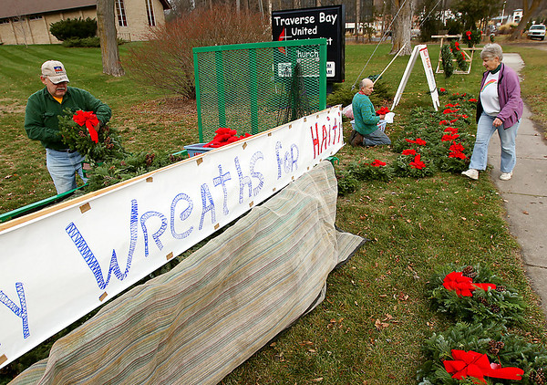 Record-Eagle/Keith King<br /> From left, Mike Windover, of Traverse City; Jerry Konczal, of Maple City; and Mike's wife, Carla Windover, arrange wreaths Saturday in front of Traverse Bay United Methodist Church along Bay Street in Traverse City for the Wreaths for Haiti sale. Money raised through the sale will go toward the construction of houses in Meillier, Haiti, during a mission trip planned for Feb. 7-17. The Windovers and Konczal are members of the Grand Traverse District United Methodist Volunteers In Mission team through Traverse Bay church. The wreaths will be on sale is again on Saturday, Dec. 3, from 10 a.m. to 4 p.m.