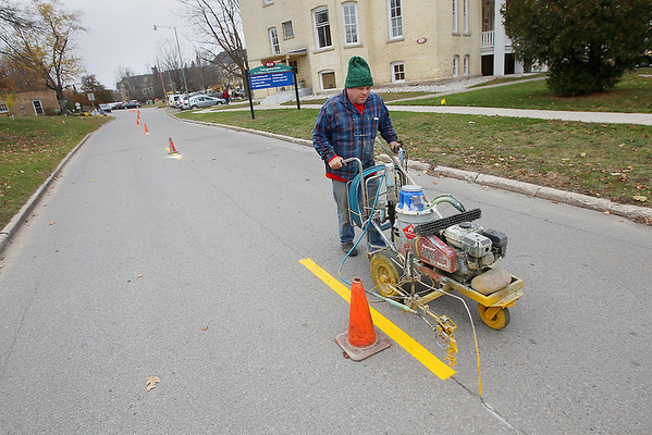 Record-Eagle/Keith King<br /> Mike Greilick, of Traverse City, paints pavement markings along Cottageview Drive at the Village at Grand Traverse Commons.