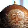 Record-Eagle/Jan-Michael Stump<br /> Diane Avery paints St. Nicholas images on driftwood and other items, such as this globe.
