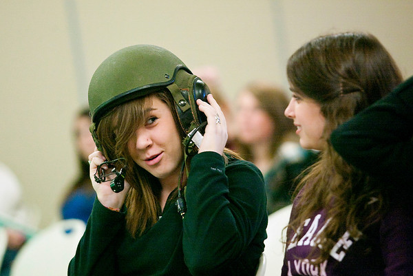 Record-Eagle/Jan-Michael Stump<br /> Traverse City Central student Jenna Becker, 15, tries on a helmet brought by staff Sgt. Sharon Whitcher, a heavy equipment mechanic with the Army National Guard, during the ninth annual GirlTech non-traditional career seminar Wednesday at the Great Lakes Campus of Northwestern Michigan College.