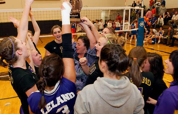 Record-Eagle/Douglas Tesner<br /> Leland coach Beth Osorio, center, hoists the Class D regional trophy as her team celebrates on Thursday.