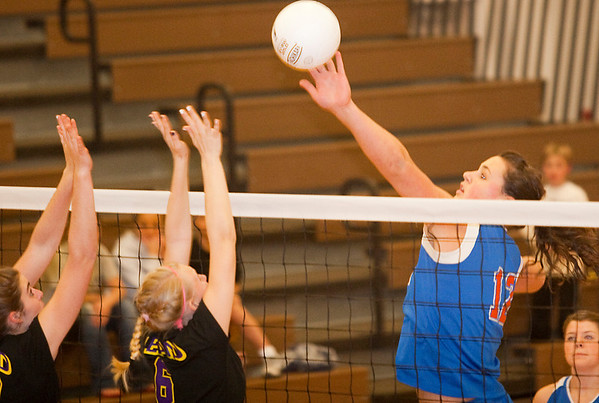 Record-Eagle/Douglas Tesner<br /> Central Lake's Jasmine Hines (12) tips the ball past Leland's Sarah Ruszel (left) and Samantha Nowak on Thursday during the Class D regional final at Buckley. Leland won in straight sets for their first title since 2006.