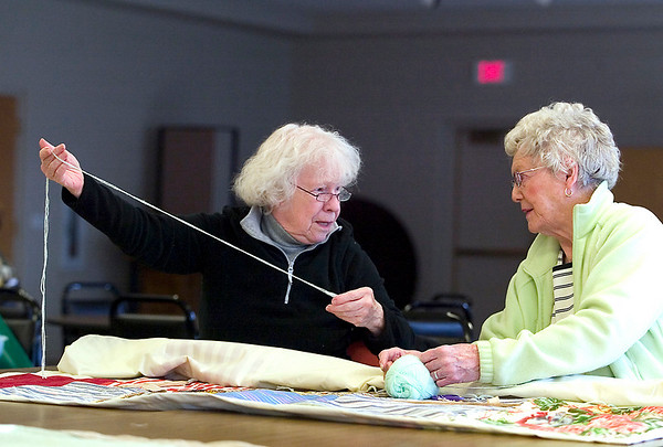 Record-Eagle/Jan-Michael Stump<br /> Jacquelyn Rossfeld, left, and Ruth Boerman, of Bethlehem Lutheran Church, talk while working on a quilt with other church members. The group meets weekly on Tuesday mornings to make quilts for Lutheran World Relief. They have made 600 so far this year and 10,000 since 1986. Groups from across the U.S. make quilts, which are gathered every October. They then are stored in Maryland, where they can be distributed to wherever there is a need, such as after a hurricane or earthquake.