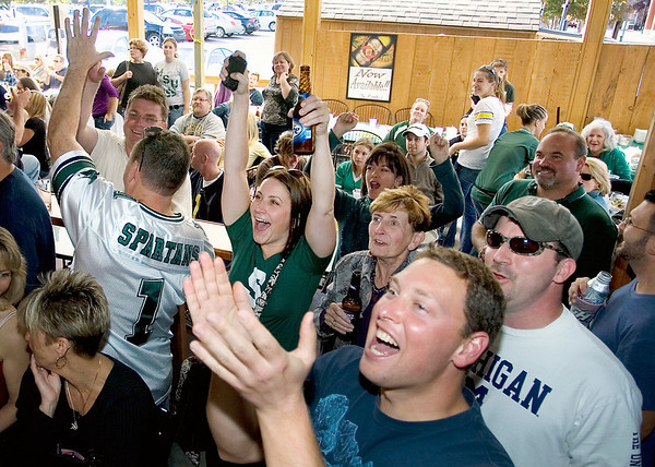 Record-Eagle/Keith King<br /> Krista Weaver, of Fenton; her mother, Carol Weaver, of Linden; Tom Roosevelt, of Traverse City, right; and Westley Benson, of Madison, Wis., foregorund, cheer Saturday at the State Street Grill during the Michigan State vs. University of Michigan football game. Krista graduated from MSU in 1995, Benson graduated from MSU in 1998.