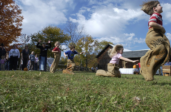 Record-Eagle/Garret Leiva<br /> David Riess, 6, of Traverse City, nears the finish line in a sack race as some of his fellow competitors fall at the seventh annual Harvest Gathering at the Samels farm Sunday in Williamsburg. The festival featured tours of the farm, barns and outbuildings dotting the grounds of the turn-of-the-century farm on Skegemog Point Road. The Samels Family Heritage Society put on the festival featuring numerous demonstrations, including a blacksmith shop, an apple press, shingle making and grain milled with power from a 'hit and miss' engine.