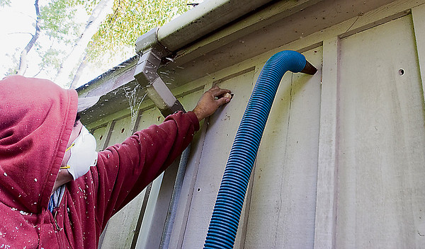 Record-Eagle/Douglas Tesner<br /> Jim Carsten, an employee at Alpers Insulation LCC, pumps insulation between the walls of a home owned by Gordon Iacovoni during a home improvement project.