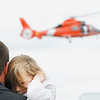 Record-Eagle/Jan-Michael Stump<br /> Gwendolyn Brush, 4, of Kingsley, covers her ears from the noise of a HH-65C Dolphin helicopter while in the arms of her father, Nathan, during a rescue demonstration at United States Coast Guard Air Station Traverse City's open house.