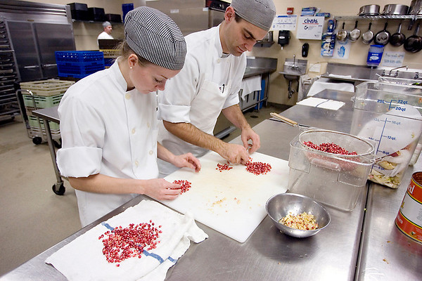 Record-Eagle/Keith King<br /> Sarah Schepers, left, and Scott Adams prepare pomegranate seeds that were used in a garnish Friday during a benefit dinner at Lobdell's Restaurant in the Hagerty Center of Northwestern Michigan College. The dinner, which benefited the Fresh Food Partnership, is sponsored by the Great Lakes Culinary Institute and the American Culinary Federation.