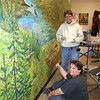 Record-Eagle/Loraine Anderson<br /> Lori Taylor, front, and Marie River put finishing touches on a mural at the the Boardman River Nature Center on Friday.  They started the project Monday.