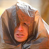 Record-Eagle/Jan-Michael Stump<br /> Coast Guard AST3 Stephen Gonzalez demonstrates the use of a garbage bag as shelter during Air Station Traverse City's annual land and water survival training Wednesday morning at Bryant Park. The training ensures crew members are up-to-date on their knowledge of equipment and skills they may need in the event of a crash or emergency landing of one of their HH-65C helicopters.