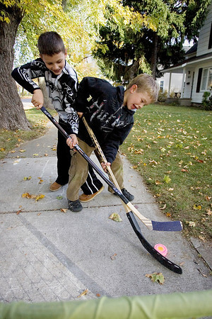 "Record-Eagle/Keith King<br /> Trevor Schuiling, left, 8, and Mack Shane, 5, both of Traverse City, play hockey Monday on the sidewalk in front of their homes. ""They're out here doing something every afternoon; it's usually this,"" said Mack's father, Steve Shane."