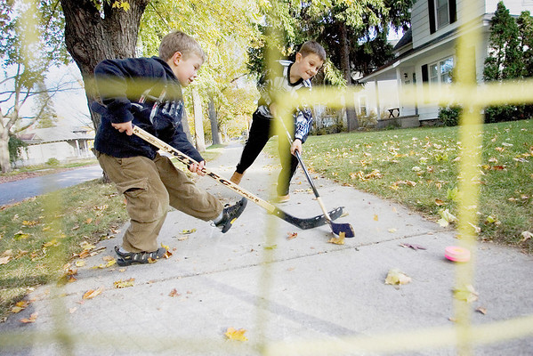 Record-Eagle/Keith King<br /> Mack Shane, left, 5, and Trevor Schuiling, 8, both of Traverse City, play hockey Monday, October 18, 2010 on the sidewalk in front of their homes.