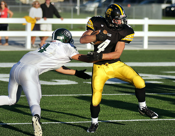 Record-Eagle/Keith King<br /> Traverse City Central's Ryan Verschuren tries to escape the grasp of Forest Hills Central's Collin Schlosser Thursday, August 26, 2010 at Thirlby Field.