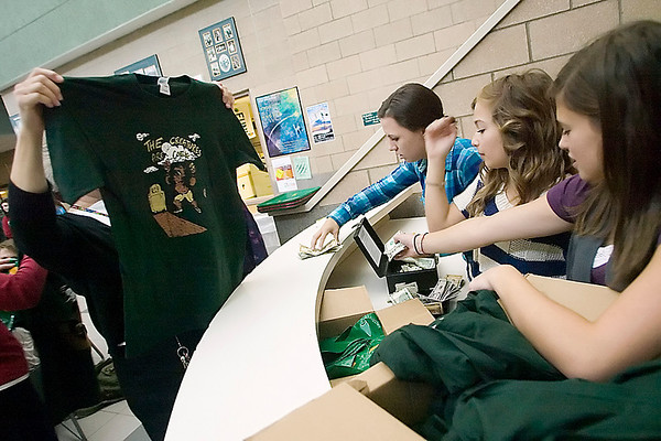 Record-Eagle/Jan-Michael Stump<br /> Traverse City West student senate members, from left, Sydney Denoyer, Isabella Mack and Alex Bondy sell t-shirts for Friday's rivalry game against Traverse City Central during Thursday's lunch.