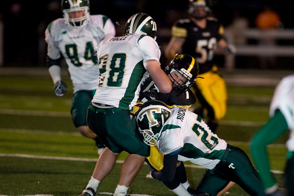 Record-Eagle/Jan-Michael Stump<br /> Traverse City Central's Tyler Clark (7) gets hit by Traverse City West's Collin Richards (27) and Matt Beem (25) in the first half.