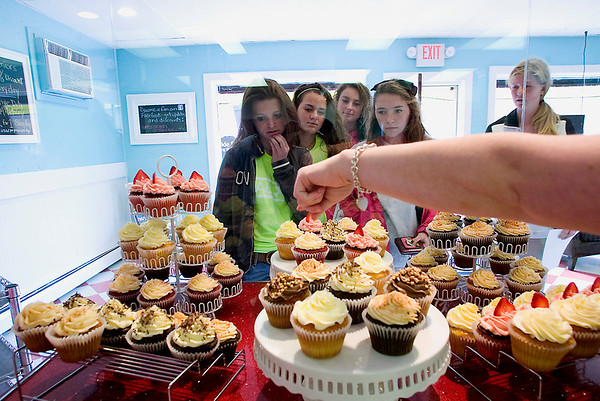 Record-Eagle/Jan-Michael Stump<br /> Sarah Smyka points out cupcake choices to, from left, Midi Battle, Molly Tompkins, Katie Knudsen, Chelsea Saunders and Anna Krueger at Simply Cupcakes on East Front Street.