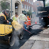 Record-Eagle/Douglas Tesner<br /> Dean Edgecomb II, employed by Team Elmer's, uses a small roller to compress blacktop that has been laid on Park Street in downtown Traverse City.