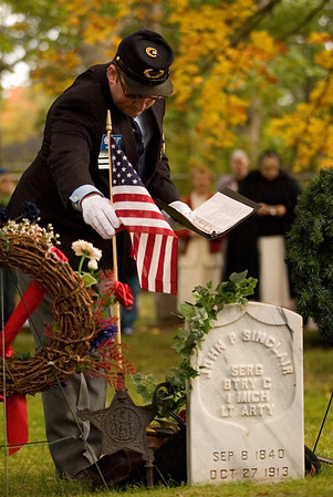 Record-Eagle/Jan-Michael Stump<br /> Jeff Morse of The Robert Finch Camp No. 14 Sons of Union Veterans of the Civil War, of Traverse City, places a flag at the rededicated gravesite of Sgt. John P. Sinclair on Saturday in Oakwood Cemetery.