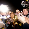 Record-Eagle/Jan-Michael Stump<br /> Traverse City Central's Phothivath Phengkhampkip (25), Max Bollinger (60) and Ronnie Saunders (27)  celebrate Friday's 25-6 win over Traverse City West with the Nowak-Olson Trophy.
