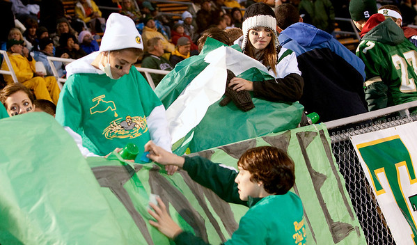 Record-Eagle/Douglas Tesner<br /> Traverse City West fans Lee Batcha, Megan Ankerson, and Joey Vanderbosch put up banners before kickoff.
