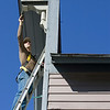 Record-Eagle/Keith King<br /> Gary Wales, owner of Wales Construction, paints trim and molding Tuesday at a commercial building on Eighth Street that is for sale. The forecast calls for plenty of sunshine and highs in the 70s at least through Sunday.