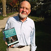 Record-Eagle/Jodee Taylor<br /> Jerry Beasley, president of the board of the Traverse Area District Library and a retired professor of the University of Delaware, holds the book of essays published in his honor.
