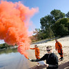 Record-Eagle/Keith King<br /> Rob Sullivan, bottom, U.S. Coast Guard Aviation Survival Technician Second Class, demonstrates how to use an MK-124 marine smoke and illumination kit alongside Brett Teuber, back left, U.S. Coast Guard Petty Officer Third Class, on Wednesday during the annual water and land survival training at Bryant Park on West Grand Traverse Bay. The training was attended by U.S. Coast Guard pilots and air crew as well as U.S. Coast Guard Auxiliary volunteers who were trained in areas such as fire and shelter building, survival techniques and utilizing a life raft, in addition to emergency signal training, with gear inspections also taking place.