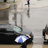 Record-Eagle/Keith King<br /> A pedestrian walks south on Park Street in Traverse City on Tuesday with an umbrella while another runs north through the rain. The forecast calls for isolated showers today with more rain this weekend.