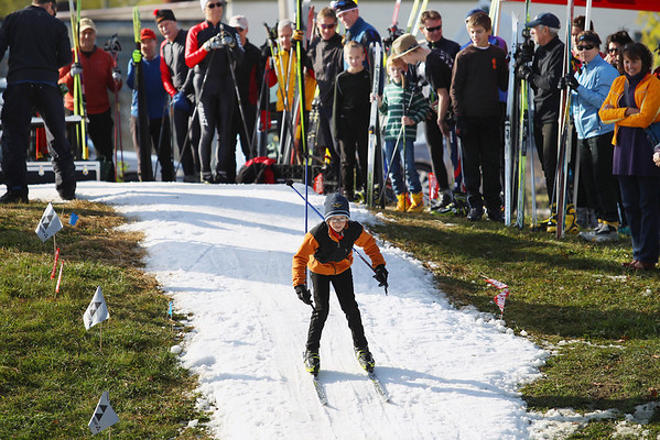 Record-Eagle/Keith King<br /> Spectators and racers look on as Spencer Todd, 11, of Grand Rapids, skis against the clock on a course at Brick Wheels during the second annual Nordic Fest. The event featured a cross-country and telemark ski swap at the Traverse City business on Eighth Street. There also was a Vasa Ski Club membership drive and party.