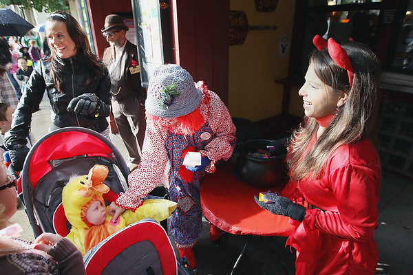 Record-Eagle/Keith King<br /> Volunteer Gina Heinzelmann, right, and Phyllis Girrbach, center, owner of Pangea's Pizza, pass out treats during the Downtown Halloween Walk in Traverse City on Friday as Brandi Brantley, left, of Traverse City, pushes her grandson, Eli Kiessel, 1, who receives a sticker from Girrbach.