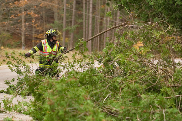 """Record-Eagle/Jan-Michael Stump<br /> Steve Hooper of the Glen Lake Fire Department clears a downed tree on South Stocking Drive near Harbor Highway outside Glen Arbor during Wednesday's wind storms. """"We haven't stopped yet, since we started this morning,"""" said Hooper."""
