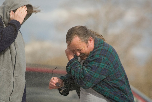 """Record-Eagle/Jan-Michael Stump<br /> Phillip Gray, right, and his son Tobias brace themselves against the blowing sand whipped up from Wednesday's wind storms Empire. """"This is the worst I've seen it,"""" in his 19 years living there, said Gray."""