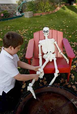 Record-Eagle/Keith King<br /> Graham Corcoran, 9, of Traverse City, attaches a leg to a skeleton decoration in his front yard Monday, October 18, 2010 in Traverse City.  Graham, along with his sister Molly Corcoran, 14, and friend Chandler Tarrant, 13 (both not pictured) were outside decorating the house and front yard with Halloween decorations.