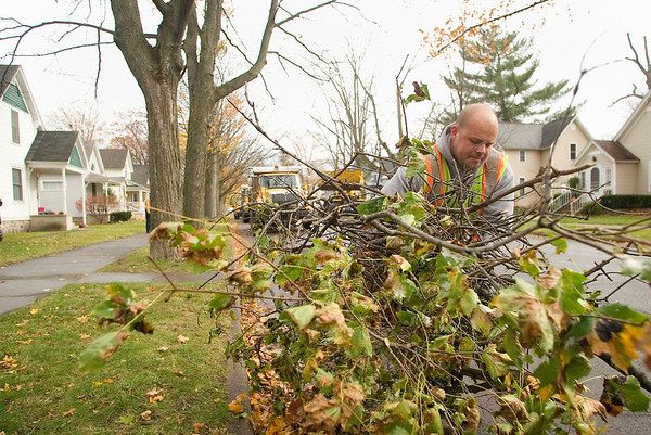 Record-Eagle/Jan-Michael Stump<br /> Rob Habedank of the Traverse City Streets Department picks up a pile of fallen tree branches on 10th Street from wind storms that passed through the area on Tuesday and Wednesday.