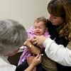 Record-Eagle/Douglas Tesner<br /> Kate Wooer holds her 15-month-old daughter Sarah as she receives an H1N1 influenza vaccine from Ruth Ann Belfi during a flu clinic held by the Grand Traverse County Health Department. The clinic gave out more than 1,300 doses of the vaccine in the Community Room of the Grand Traverse Mall.