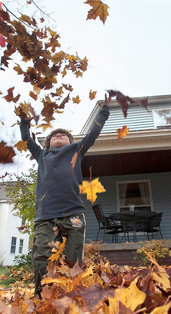 Record-Eagle/Douglas Tesner<br /> Henry Berghoef, 5, throws leaves into the air as he enjoys the warmer fall weather in Traverse City.