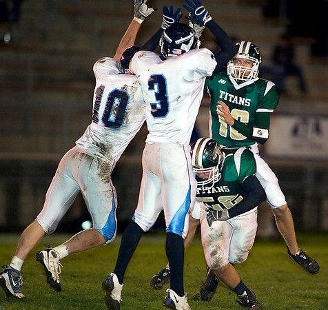 Record-Eagle/Jan-Michael Stump<br /> Petoskey defensive end Vince DeAgostino (10) and linebacker David Lewis (3) try to block a pass by Traverse City West quarterback Isaiah Hackney (16) in the first quarter of Friday's game.