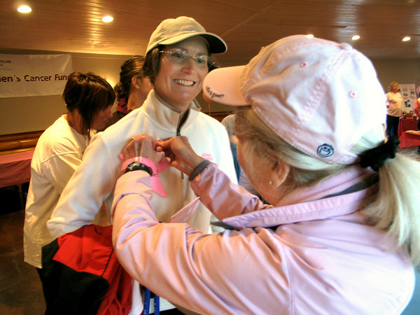 Record-Eagle/Sheri McWhirter<br /> Breast cancer survivor Michelle Honer, of Traverse City, has her pink survivor star pinned to her clothing by Remembrance Run volunteer Linda Deneen.