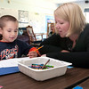 Record-Eagle/Douglas Tesner<br /> <br /> Sara Sholten looks over work Trenton Williams did in a kindergarten class at Blair Elementary School.  Enrollment in all-day, every-day kindergarten at Blair Elementary increased rapidly right before school started this year. A third section was needed.