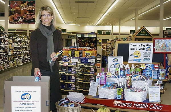 Record-Eagle/Lisa Perkins<br /> Sherri Fenton, development director of Traverse Health Clinic, deposits toothpaste into the collection box for dental health supplies located at Tom's Food Market.