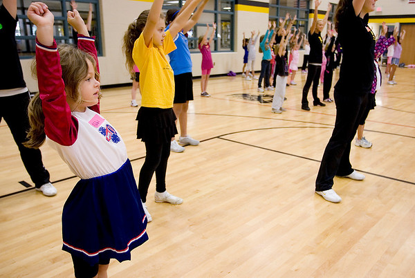 Record-Eagle/Keith King<br /> Abbigaile Panks, 6, of Traverse City, learns a cheer during the Traverse City Central High School Cheer and Dance Team Junior Pom Clinic at Traverse City Central High School. Workshop students will perform a routine they learned, along with members of the dance and cheer teams who led the workshop, during today's Traverse City Central High School Junior Varsity football game at 4 p.m. at Thirlby Field.