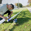 Record-Eagle/Keith King<br /> Randy Borgen, an employee with Traverse Outdoor, cleans and glues sections of PVC pipe together which will be used underground as part of an irrigation system between West Grandview Parkway and Bay Street.