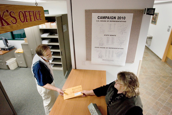 Record-Eagle/Keith King<br /> Cassandra Douglass, right, of Traverse City, hands her absentee ballot to Garfield Township Deputy Clerk Don Wilcoxen on Monday at the Garfield Township office.