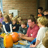 "Record-Eagle/Jan-Michael Stump<br /> Old Mission Peninsula School students watch as Pat Harrison, the ""Lord of the Gourd,"" demonstrates his pumpkin carving skills."