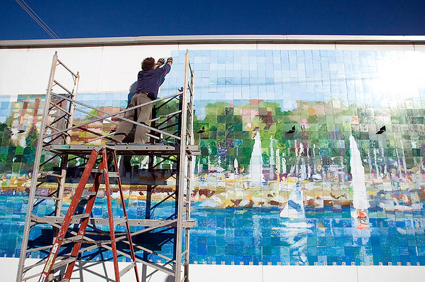 Record-Eagle/Jan-Michael Stump<br /> Artist Terry Dickinson (cq) places the last few tiles on the Community Mural Mosaic Project Tuesday morning on the South wall of ACE Hardware on West Front Street. There are 2,600 six-inch tiles on the 13-foot-by-50-foot mural, designed by a professional artist and painted by members of the public at a number of area events under assistance from professionals. Dickinson directed the project, which was initiated by Artcenter Traverse City. The center will host a party Saturday, Nov 6, 2010, at the mural starting at 3 p.m.