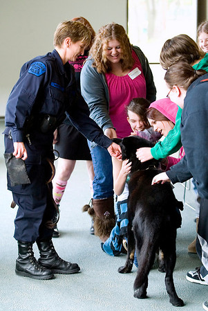 Record-Eagle/Jan-Michael Stump<br /> Students pet dog Jett with Michigan State Police Trooper Kris Mikowski, left, following Mikowski's session on her work as a K-9 officer during the 10th Annual GirlTECH non-traditional career seminar for 10th-grade girls.