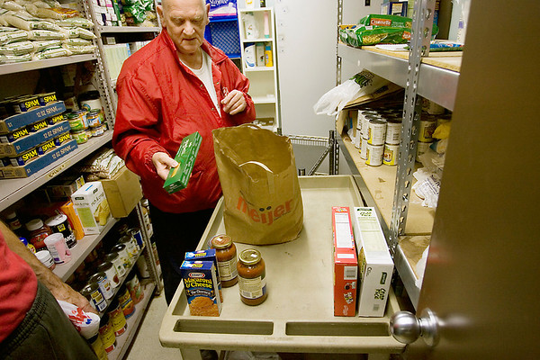 Record-Eagle/Keith King<br /> Volunteer Carroll Denzel, of Traverse City, takes donated food out of a bag Thursday, November 4, 2010 prior to the food being taken to the downstairs food pantry at the Salvation Army in Traverse City.