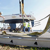 Record-Eagle/Jan-Michael Stump<br /> A group of boatowners remove their sailboats from the water at Elmwood Township Marina on Saturday. They hired a crane to assist them because it cost less than the amount the marina charges.