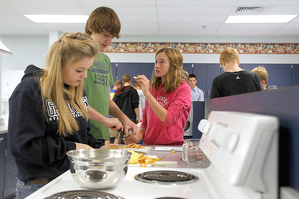 Record-Eagle/Jan-Michael Stump<br /> Sarah Hartman, Theo Noffsinger and Kasie Aguayo peel, core and slice apples to make apple chips Thursday in Kathy Hartman's health and foods class at Suttons Bay High School.